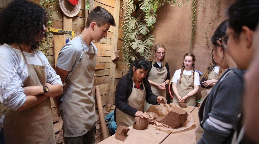 Voluntarios en Perú aprendiendo a usar arcilla en un taller durante su voluntariado social en verano.